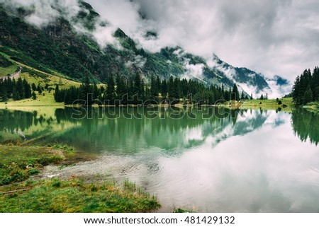 Environment of the alpine lake on a rainy day. Beautiful green alpine valley.