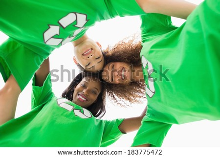 Environmental activists embracing and looking down at camera on white background - stock photo
