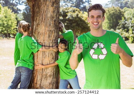 Environmental activists hugging a tree in the park on a sunny day - stock photo