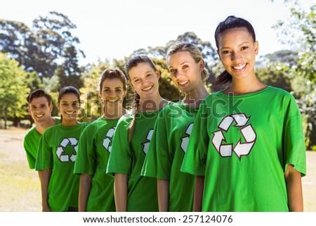 Environmental activists smiling at camera on a sunny day - stock photo