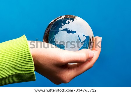 Environmental concept with blue glass globe in hand, Europe - stock photo