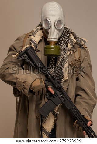 Environmental disaster. Post apocalyptic survivor in gas mask with rifle. - stock photo