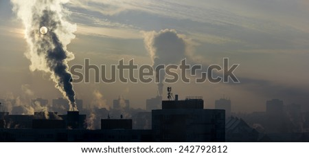Environmental pollution. It is very cold in the morning sunrise, with smoking chimneys. - stock photo