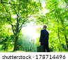 Environmentalist Businessman in Green Forest - stock photo