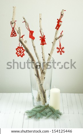 environmentalist christmas tree from white birch twigs, with red felt ornaments on bright wooden table  - stock photo