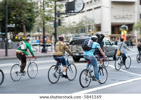 Environmentally conscious bikers in traffic in San Francisco, California. Motion blur on the subjects - faces unrecognizable. - stock photo