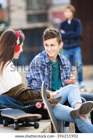Envy male teen standing aside of girlfriend talking with boy outdoors - stock photo