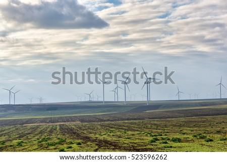 Eolian field and wind turbines farm on a cloudy day
