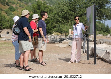 EPHESUS, TURKEY - JUNE 6, 2014: A group of tourists gather around a tour guide in the celsus library area of Ephesus in order to hear the guide tell them about the site. - stock photo