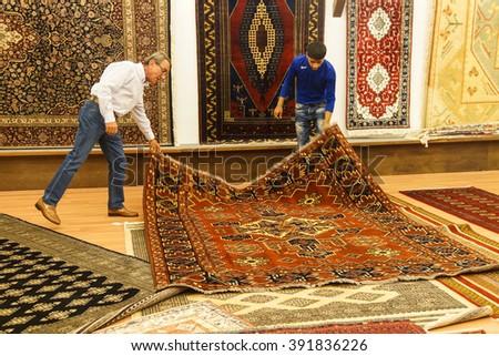 EPHESUS, TURKEY - MAY 25, 2014 - Merchants display carpets in  Ephesus, Turkey - stock photo