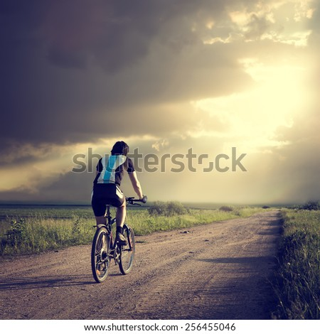 Epic Photo of Cyclist on the Country Road. Rear View. Dramatic Sky Background. Hope for Better Future Concept. Instagram Styled Toned Photo. Copyspace. - stock photo
