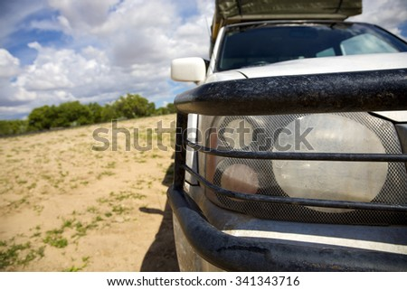 EPUPA FALLS, NAMIBIA, JANUARY 7: Front view of protection bars and headlights from off road vehicle in the Kaokoland with the bush and cloudy blue sky in the background, Namibia 2010 - stock photo