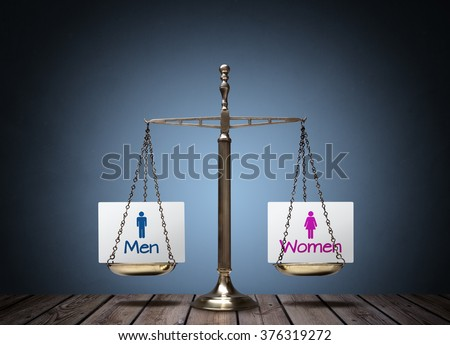 Equality between man and woman concept with beam scales and sign - stock photo