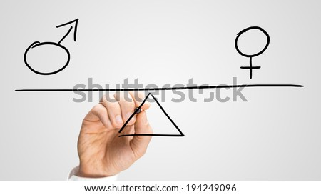 Equality between the sexes depicted in a conceptual image by a man drawing a seesaw showing the male and female genetic symbols in equilibrium. - stock photo
