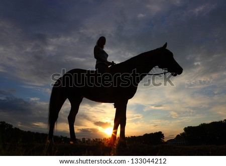 Equestrian girl at sunset