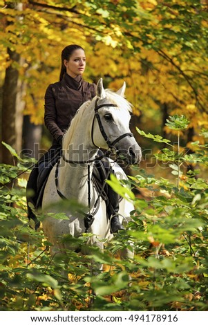 Equestrian model with her horse in autumn nature