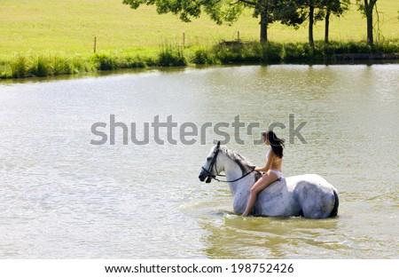 equestrian on horseback riding through water - stock photo