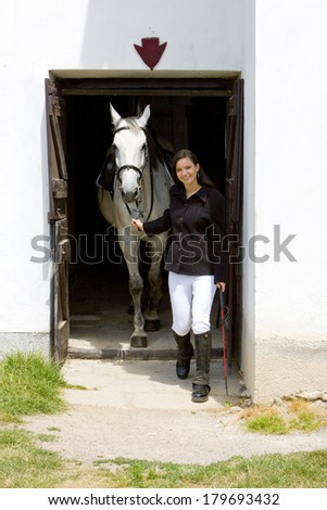 equestrian with horse in stable - stock photo