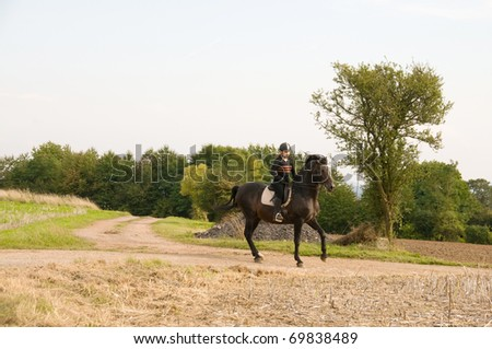 Equestrienne rides at a gallop on a brown horse.