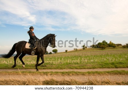Equestrienne rides at a gallop on the field road.