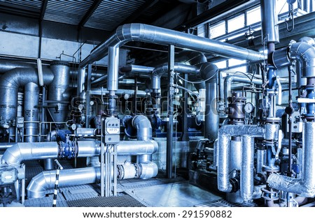 Equipment, cables and piping as found inside of a thermal power station in blue tones. - stock photo