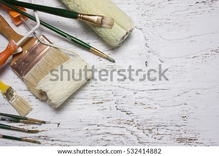 Equipment for paint on the white wooden background.