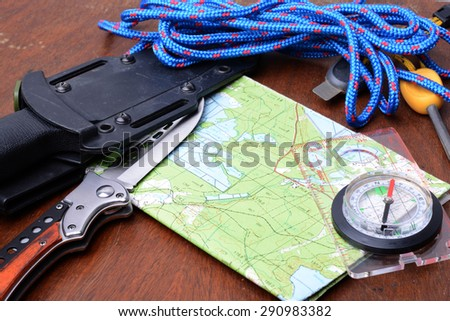 Equipment for survival. Map, knife, rope, compass, fire striker. - stock photo
