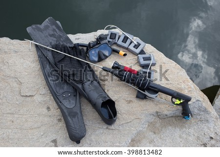 Equipment for underwater hunting near the pond on the rock.