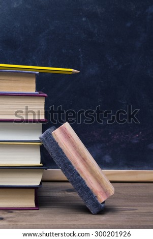 eraser, pencil with books and blackboard background - stock photo