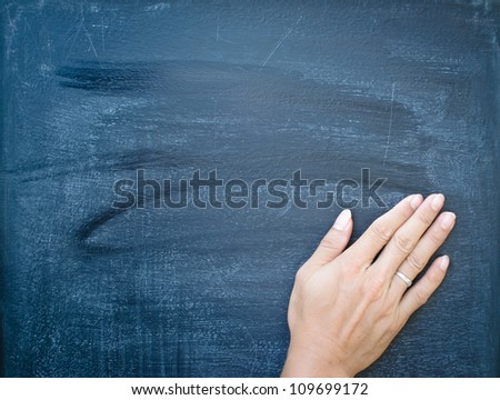Erasing the chalkboard by hand - stock photo