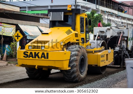 ERAWAN Thailand - August 13, 2015: Road repairing on ERAWAN Thailand city. Tracked paver laying fresh asphalt pavement during road repairing.