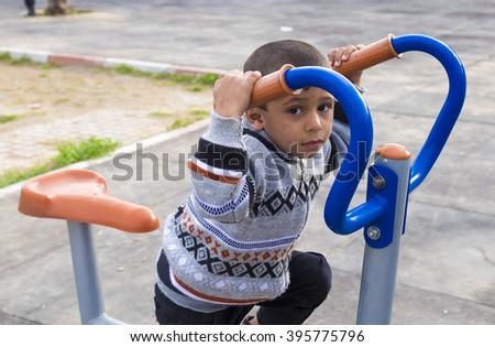 Erbil, Iraq - February 1, 2016: Orphan syrian child inside park in Kurdistan region in Erbil - stock photo