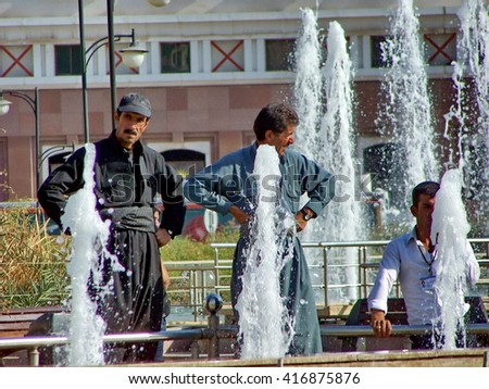 ERBIL, IRAQ, KURDISTAN - CIRCA NOVEMBER 2011: Kurdish men relax in a city park with fountains at the base of the Citadel archaeological area on a plateau