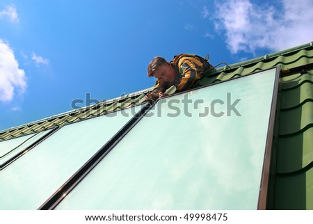 Erector of solar water heating system on the roof.