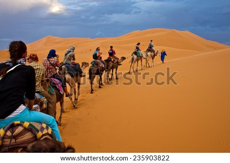 ERG CHEBBI, MOROCCO - AUGUST 3: Camel caravan with tourists in the desert on August 3, 2010 in Erg Chebbi, Morocco. Erg Chebbi is part of Sahara desert. - stock photo