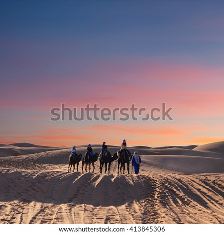 ERG CHEBBI, MOROCCO - JANUARY 6, 2014: Caravan of tourists crossing in desert in Western Sahara, Morocco. Tourism is an important item in the economy of Morocco.
