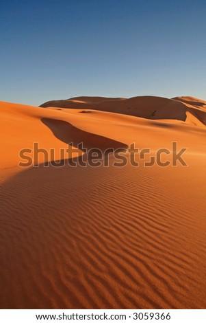Erg Chebbi sand dunes in the Sahara Desert near Hassi Labiad and Merzouga, Morocco. Algeria is located 20 km from here. - stock photo