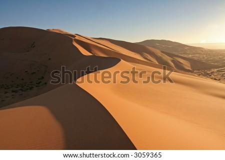 Erg Chebbi sand dunes on sunrise in the Sahara Desert near Hassi Labiad and Merzouga, Morocco. Algeria is located 20 km from here. - stock photo