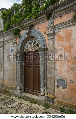 ERICE, ITALY MAY, 26, 2013: Retro wooden door outside old Italian wall in Erice, Sicily, Italy