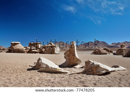 eroded rocks laying in the sand of the altiplano desert of the andes near border Bolivia and Chili South America wind erosion in the high andes desolated landscape