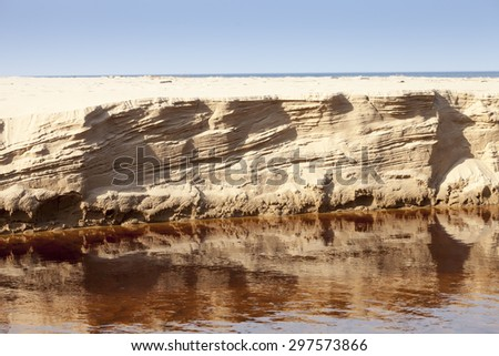 Eroded sand riverbank after High flows - stock photo
