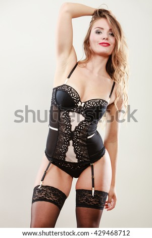 Erotic and provocative. Sensual attractive long haired female model posing in lacy black sexy lingerie in studio. - stock photo