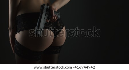Erotic back view of a female body with  gun - stock photo