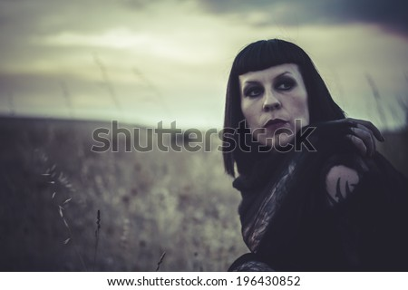 erotic brunette woman dressed with black spider web, sunset