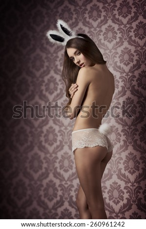 erotic easter portrait of charming young woman with long hair and lace panties showing her perfect naked body and wearing fluffy bunny easter and tail  - stock photo