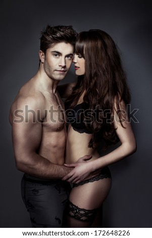 Erotic portrait of an attractive sexy young couple posing holding each other intimately in their underwear with the woman wearing black lacy stockings - stock photo