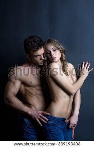Erotica. Strong man touching sensual woman - stock photo