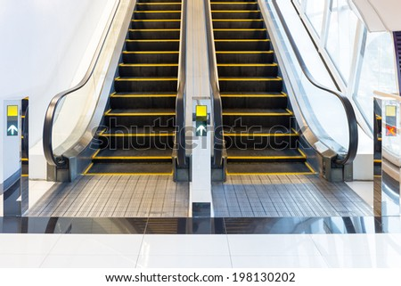 Escalator(black and metallic color) in shopping mall. - stock photo