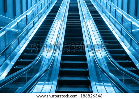 escalator blue two tone color going up stair in building  - stock photo