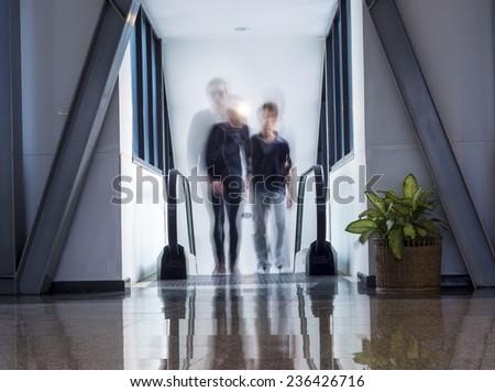 escalator leading upward, people walk out creating motion blur - stock photo
